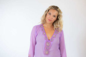 Pretty blonde woman in lila caftan smiling on white background Banque d'images - 152826631